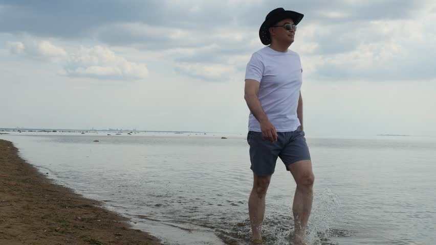 Adult man in white t-shirt and black cowboy hat walking along sea shore, Summer beach weekend, The gulf of Finland coast, 4k shot | Shutterstock HD Video #1015345525