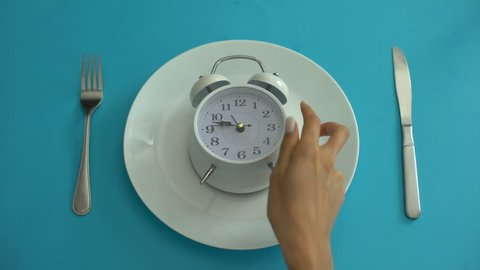 Alarm clock on plate, adhere to diet time, proper nutrition, discipline, closeup
