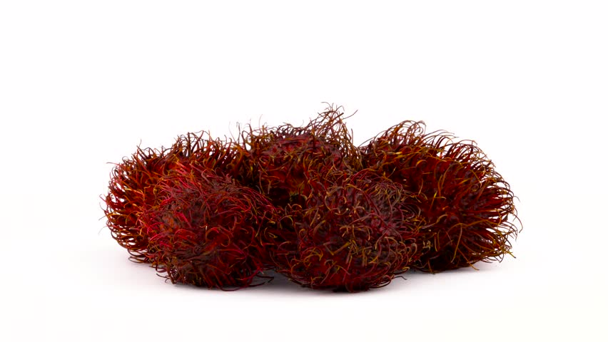 A heap of red color rambutan fruits. Rotating on the turntable isolated on the white background. Close up. Macro.