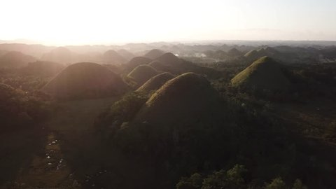 Aerial footage of the Chocolate Hills with sunlight and village smoke in Bohol, Philippines