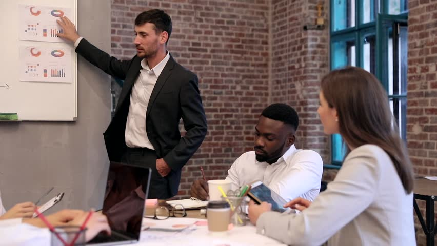Team of Young Business People Sitting around Office Table. Making Notes in the Tablet, Notebooks. Team Leader Talking with his Collegues. Explaining his Future Project. Pointing on Graphs and Charts. | Shutterstock HD Video #1015381495