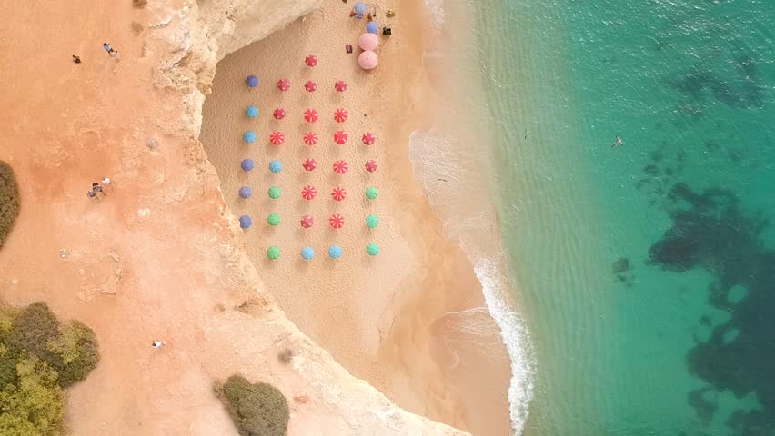Drone shot of beach under cliffs with parasols in Algarve, Portugal. PANING LEFT | Shutterstock HD Video #1015382755