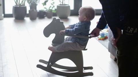 Boy toddler baby swinging on a rocking chair in the shape of a horse, slow motion
