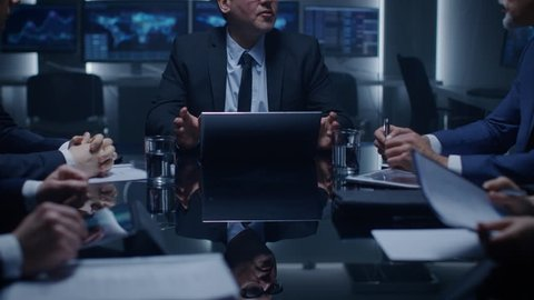 Senior Government Official Holds an Emergency Meeting with His Team of Advisors. Director Gives Orders to His Subordinates. In the Background Monitors with Various Data. Shot on RED EPIC-W 8K Camera.