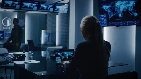 Female Special Agent Works on a Laptop in the Background Special Agent in Charge Talks To a Military Man in the Monitoring Room. Shot on RED EPIC-W 8K Helium Cinema Camera.