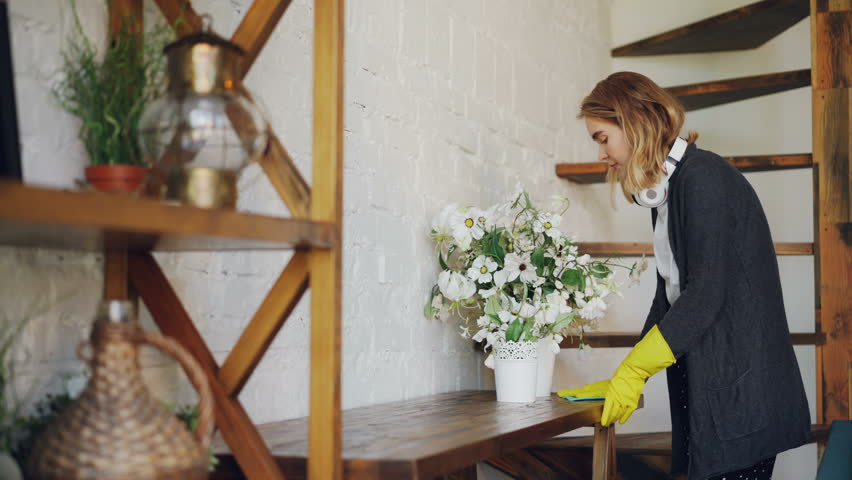 Professional Housekeeper Is Dusting Furniture With Wet Cloth Woman Is Wearing Protective Gloves Casual Clothing And Headphones