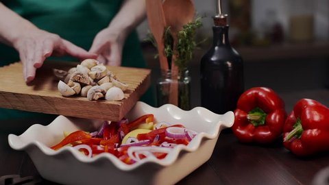 The cook makes meal with champignons and vegetables, chef adds champignons to the meal, vegetarian and gealthy recipe to cook at home, food with mushrooms