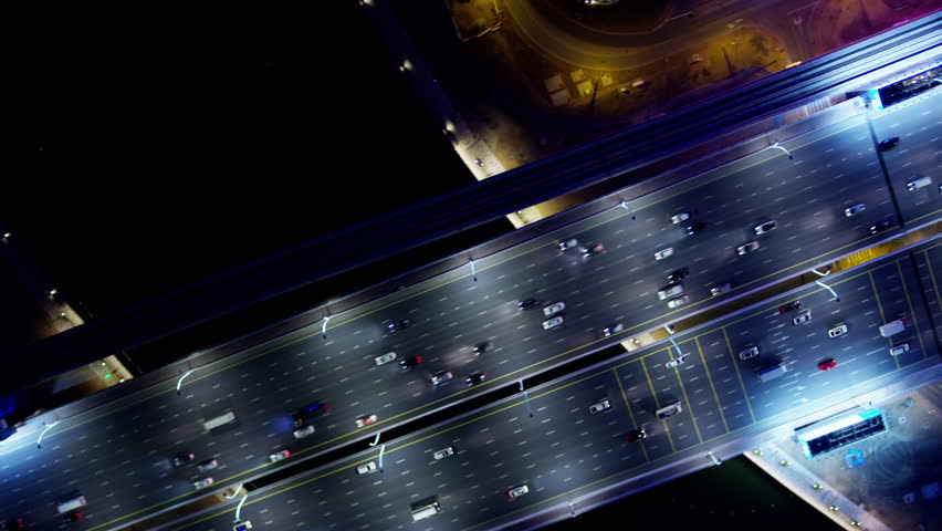 Aerial illuminated night overhead view city highway commuter vehicle traffic metro rail commercial area modern vehicle transport system UAE Middle East Dubai RED WEAPON