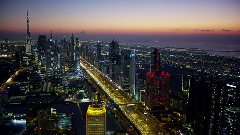 Dubai - March 2018: Aerial night illuminated city view Sheikh Zayed road skyline skyscrapers commercial condominiums vehicle transport highway metro UAE RED WEAPON