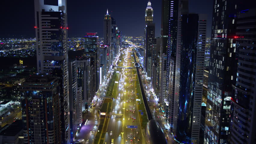 Aerial night illuminated city view Sheikh Zayed road skyline skyscrapers commercial condominiums suburbs vehicle transport highway metro UAE Dubai RED WEAPON