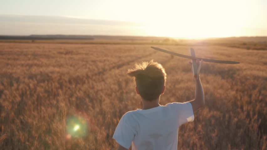 Happy child runs with a toy airplane on a sunset background over a field. The concept of a happy family. Childhood dreams | Shutterstock HD Video #1015451845