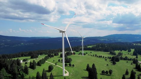 Wind Turbines Mont Soleil Switzerland aerial shot iconic view. Two beautiful windmills on a hill, scenic panorama in the background