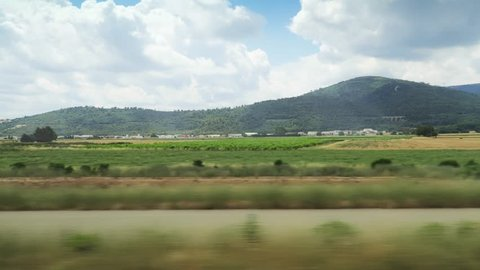 Beautiful view to a picturesque green landscape from the window of the moving train. Summer peaceful countryside with boundless fields, distant buildings and hills on the horizon.