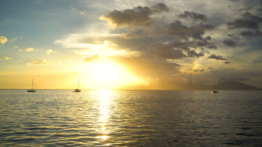 Polynesian golden sunset view of reef and yachts in a tropical Island paradise Moorea from Tahiti South Pacific ocean sun flare | Shutterstock HD Video #1015457485