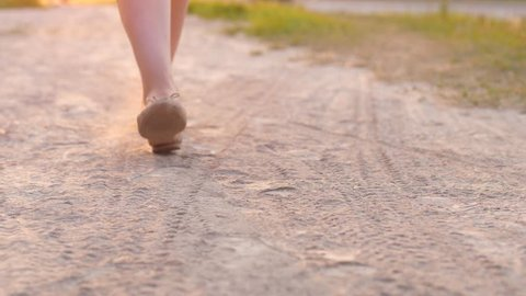 Woman feet in flat shoes walk on dust road at hot summer day