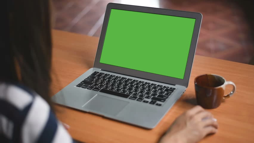 Over the shoulder shot of a business woman working in office interior on pc on desk, looking at green screen. Office person using laptop computer with laptop green screen, sitting at wooden table