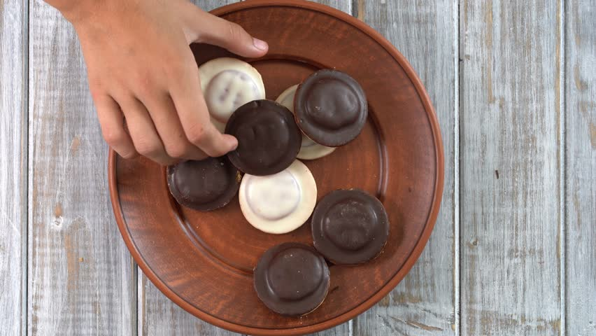Plate full of biscuits with glaze being snatched up by five hungry children girl.  Close up, top view, macro