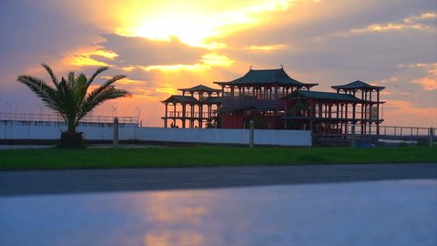 beautiful sunset against the backdrop of palm trees and chinese house.