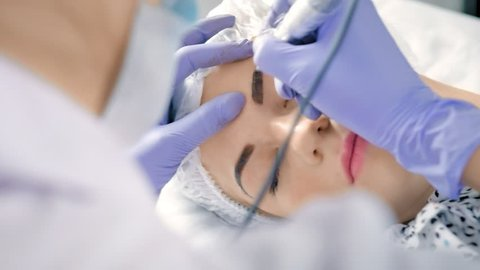 High angle beautician specialist of permanent makeup making brow microblading tattooing make up
