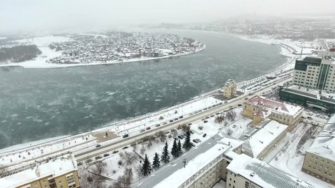 Aerial drone high flight above main ambenkment frozen winter Angara river icebergs from Baikal. Center of Irkutsk city old village. Slow blizzard extreme cold weather. Tourism in Russia commercial.