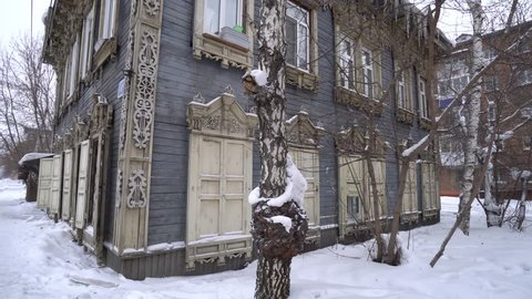 Cold Siberian winter wooden old house corner. Unique authentic Russian style wood carving architecture. Irkutsk center tourist attraction. White snow wind blizzard. Gimbal professional 4k