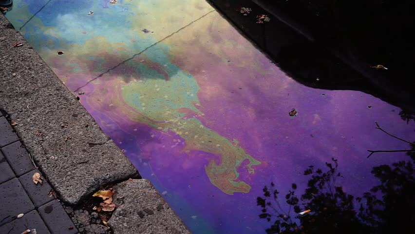 Puddle of a sidewalk with traces of diesel oil on the water  | Shutterstock HD Video #1015564945