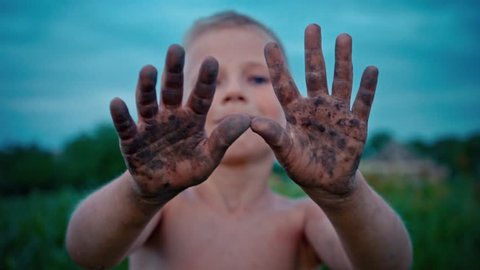A happy child shows his hands dirty from the ground, a boy smeared in the mud, a merry childhood pastime