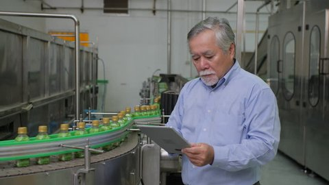 A male factory manager in beverages manufacturing industry looking at computer tablet and checking the quality of the product. Production of drinking water and beverages.