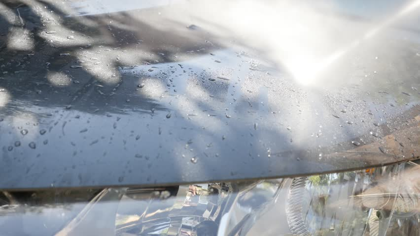 Hood and headlights washing with automatic pressure car washer slow-mo close-up video