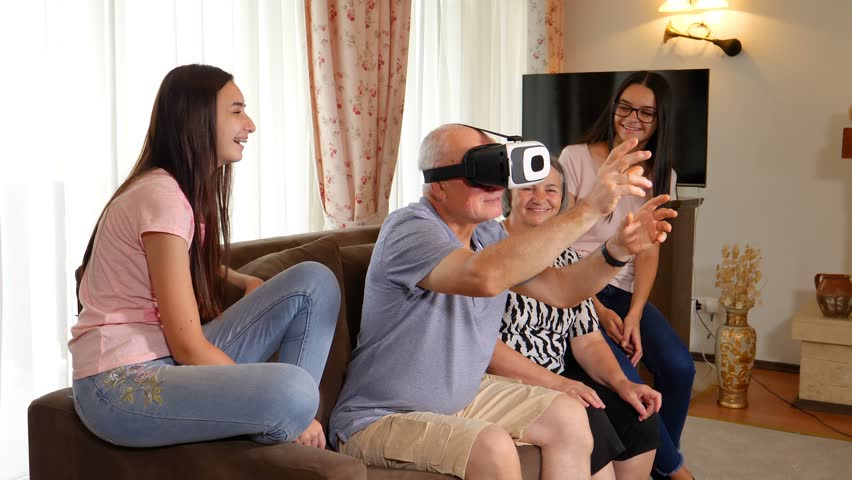 a38a05cca04 Senior man in virtual reality headset or 3d glasses having fun with his  wife and granddaughters. Senior man wearing virtual glasses at home.