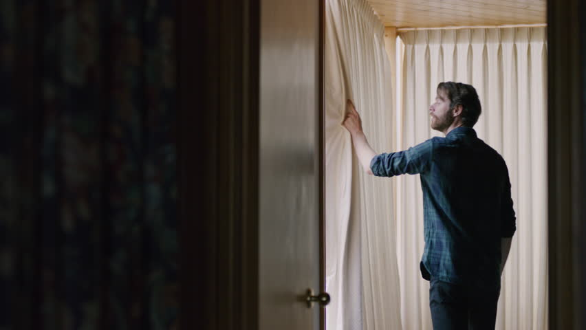 Young bearded man opening window curtains in a dark room. Shot with a RED camera. 4k footage.