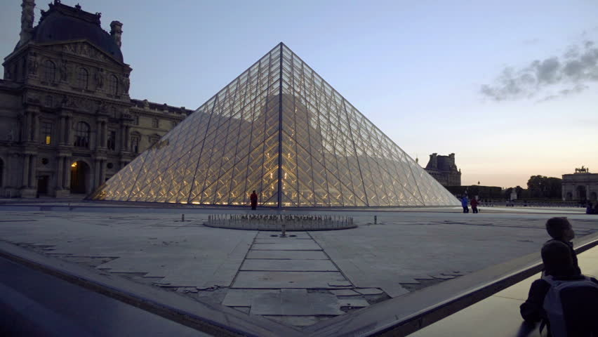 PARIS - MAY 4, 2018: Le Louvre pyramid at sunset, early evening lights, 1080 HD Paris France Europe. The historic museum opened on August 10 of 1793 with an exhibition of 537 paintings. | Shutterstock HD Video #1015617565