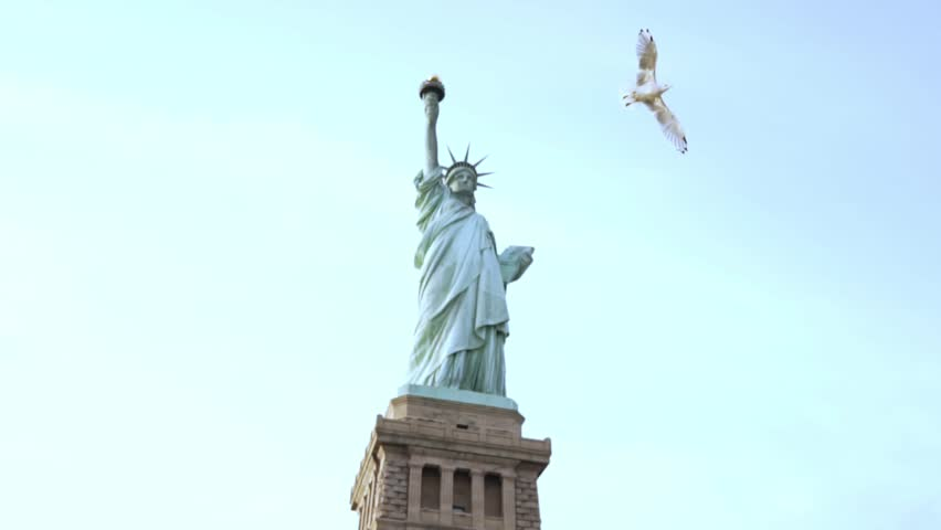 Famous Statue of Liberty national monument on Liberty Island in New York on a clear summer day, a big bird flying by.