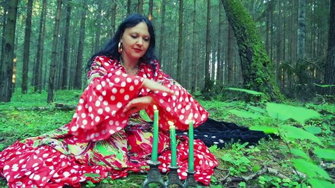 A gypsy woman fortune-teller in the forest performs magical actions with her hands and blows out candles.