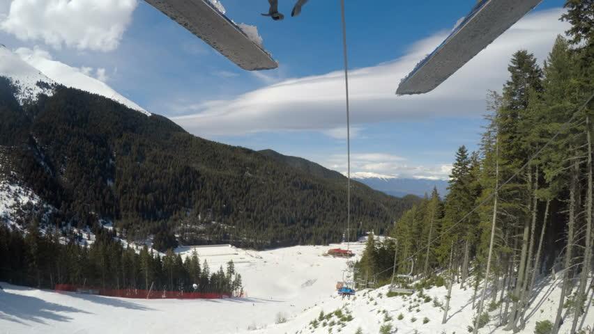 POV backwards to black Tomba slope from skier riding on ski lift in Bansko, Bulgaria
