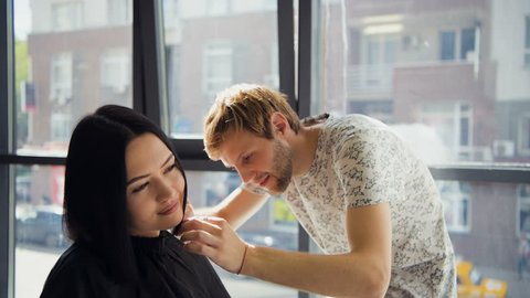 At the hairdresser's, smiling brunette woman getting her hair done in the beauty salon by male hairdresser in front of a big window