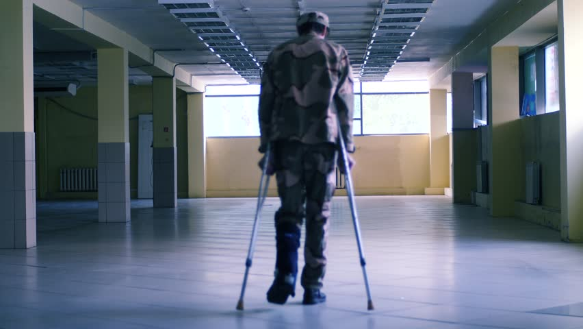 Soldier on crutches with dog in the big hall slow motion shot