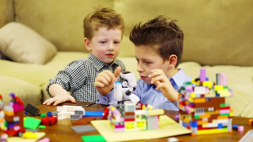 Two happy boys play with robot and with tinker toys, slow motion