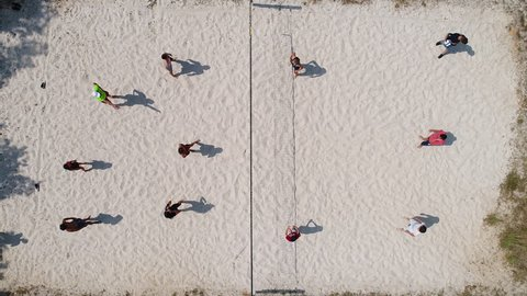 Group of people playing beach volley ball. Aerial vertical view