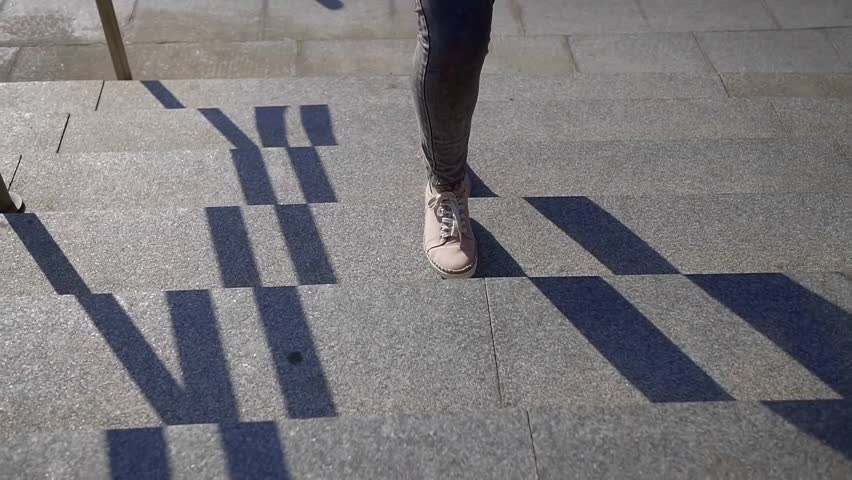 Close-up of woman legs in pink shoes and jeans climb the stone stairs up on a Sunny day