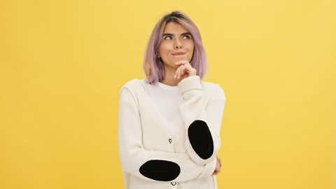 Pensive smiling woman in warm cardigan looking around over yellow background