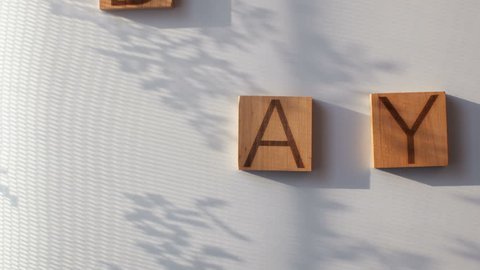 "The word ""DAY"" is laid out in wooden letters"