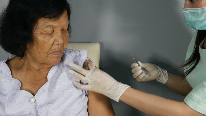4k video of Doctor injecting flu vaccine to patient's arm in local hospital