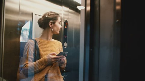 Young happy woman riding elevator with glass wall up, door opens and she walks out smiling using smartphone shopping app