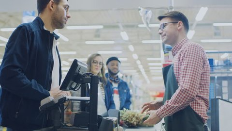 At the Supermarket: Checkout Counter Happy Customer Chats with Friendly Cashier who Scans Fresh Groceries and Fruits. Modern Shopping Mall with Wireless Paying Terminal System.