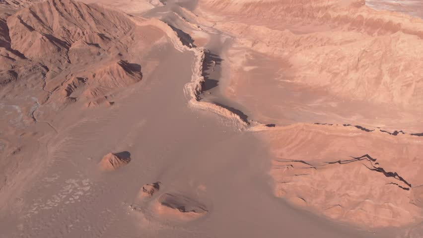 Cinematic aerial view of rocky mountain Atacama desert Chile. Drone flying forward, filming down and slowly tilting up reviling mountains and snowy volcanoes in background far. Valle de la Luna.