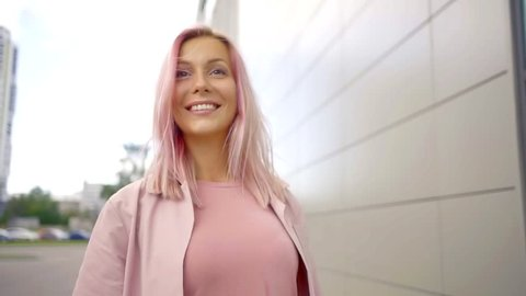 smiling adult woman with unusual pink hair color is walking in street in daytime, spinning her lock of hair