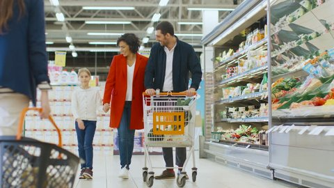 At the Supermarket: Happy Family of Three, Holding Hands, Walks Through Fresh Produce Section of the Store, Holding Hands. Father, Mother and Daughter Having Fun Time Shopping. Shot on RED EPIC-W 8K.