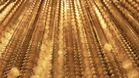 Slow, smooth movement of long gold chains. Uniform swing. Gold background for relaxation. Meditation. Relax. Texture for soothing. Glitter. View from bottom to top. Blurred
