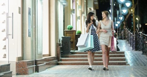 Two girls walking down broadway near shopping centers with bags in hands, then female friend joins them. Friends chatting and smiling 4k